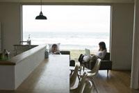 部屋でソファに腰掛ける男女とキッチンカウンター