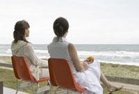 海辺のテラスでフルーツを持ちイスに腰掛けている女性2人の後姿