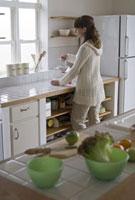 キッチンに立つ女性と台の上に並べられた食材