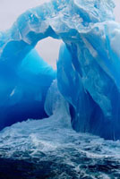 Waves surge round an ice arch on an ancient blue iceberg. An