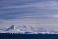 Low ice covered islands in front of the mountains on Wiencke