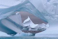 Pointed iceberg seen through a hole in an iceberg near Plene