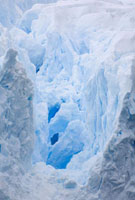A crevasse leads deep int the face of a glacier revealing ic