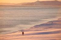 A Chukchi hunter walking along the snow covered shoreline at