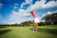 Female golfer swinging golf club.