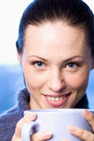 Smiling woman holding cup of hot drink