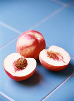 Two white nectarines, halved and whole