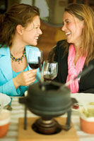 women clinking glasses at fondue meal