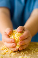 Childs hands holding grated cheese