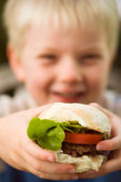 Small boy holding a burger