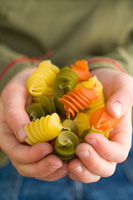Coloured pasta in childs hands
