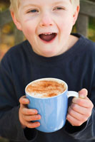 Boy holding cup of hot chocolate