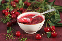 Cherry jam in small bowl with spoon