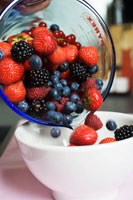 Tipping fresh berries into a bowl
