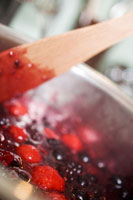 Berry jam, stirring the fruit and sugar
