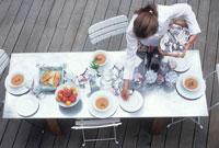 Young woman laying table 22199028179| 写真素材・ストックフォト・画像・イラスト素材|アマナイメージズ