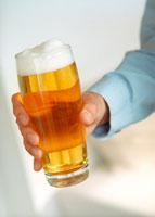 Hand holding glass of light beer
