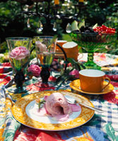 Summery table laid for coffee with roses