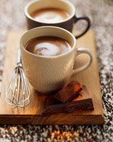 Two mugs of hot chocolate on a board