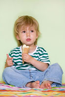 Small boy eating vanilla ice cream