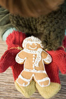 Hands in mittens holding gingerbread man