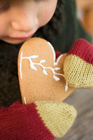Child in mittens with gingerbread heart