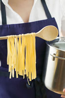 Woman holding pan and home-made pasta