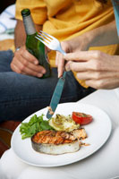 Woman eating grilled salmon cutlet