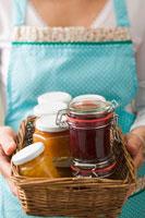 Woman holding a basket full of jam's jar 22199035676| 写真素材・ストックフォト・画像・イラスト素材|アマナイメージズ