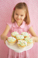 Girl holding tray of decorated muffins