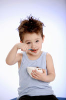 Small boy eating chocolate pudding