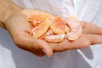 Hand holding dried mango pieces 22199036986| 写真素材・ストックフォト・画像・イラスト素材|アマナイメージズ