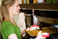 Woman putting vegetable pizza