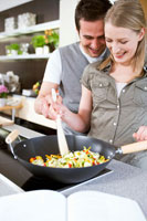 Man and woman stirring vegetables in wok