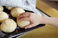 Child's hand reaching for a bread roll