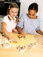 Two girls cutting out biscuits