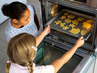 Two girls putting biscuits into the oven