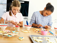 Two girls decorating biscuits
