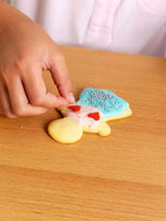 Child's hand decorating a biscuit