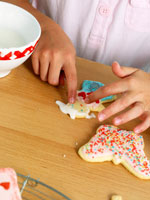 Child's hands decorating a biscuit