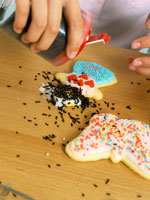 Child's hands decorating biscuits