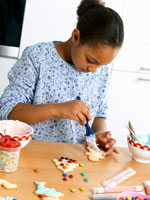 Girl brushing biscuit with icing