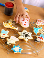 Child's hand decorating biscuits