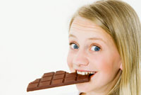 girl biting into a bar of chocolate