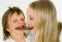 Children biting into the same chocolate