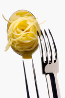 Cooked taglierini on spoon with fork