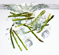 Green asparagus spears and ice cubes