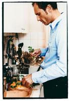 Man putting coriander on chicken