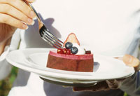Woman eating small chocolate cake
