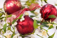 Red Christmas baubles amongst mistletoe